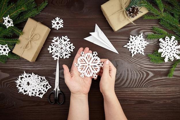 Руки держат белую снежинку на деревянном столе