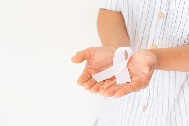 Руки держат белую жемчужную ленту