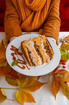Руки держат белую тарелку торт осенние листья