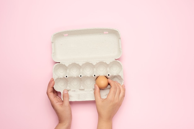 Hands holding whole brown chicken egg and paper tray