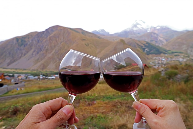 Hands holding wine glasses clinking with blurry mountains view