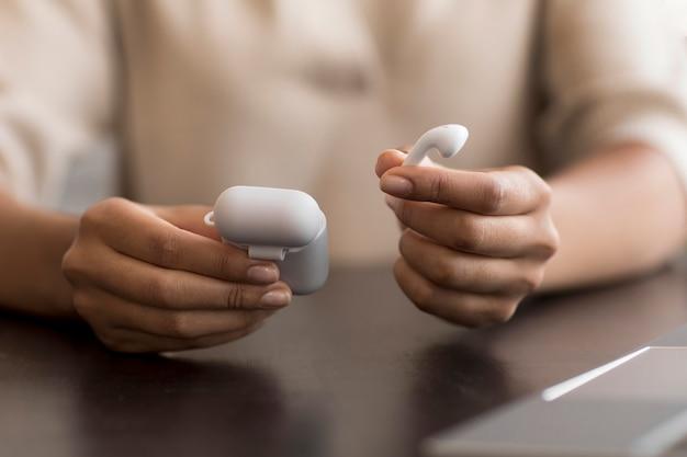 Mani che tengono la custodia per auricolari wireless