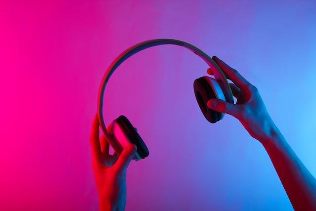 Руки держат беспроводные стереонаушники с неоновым сине-розовым градиентным светом