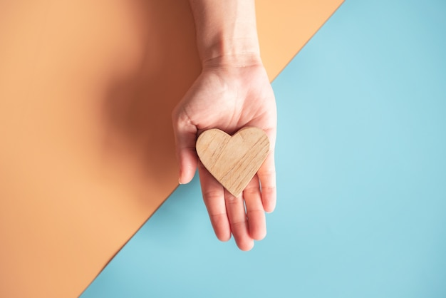 Hands holding wood heart