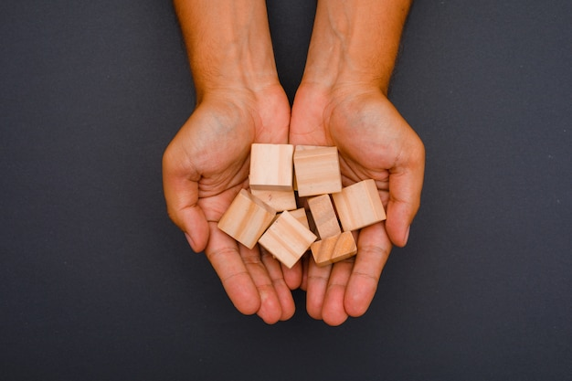 Hands holding wooden cubes.