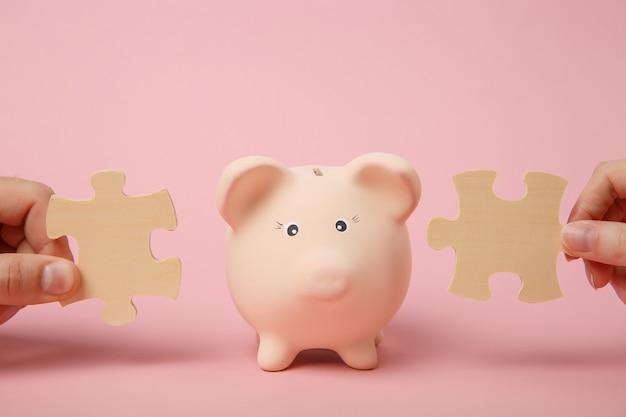 파스텔 핑크색 벽 배경에 격리된 돼지 저금통 근처에 나무 직소 퍼즐 조각을 들고 있는 손. 돈 축적, 투자. 협회 및 연결 개념입니다. 복사 공간을 비웃습니다.