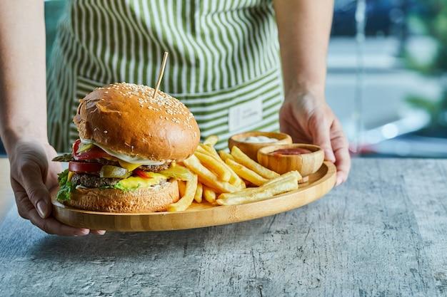 Mani che tengono un piatto di legno con hamburger e patate fritte con ketchup e maionese.