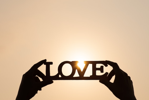 Hands holding the word love at sunset background. love concepts.