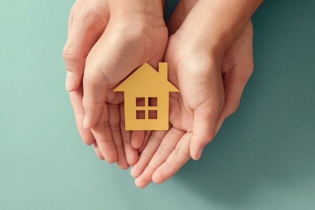 Hands holding yellow paper house on blue surface, family home, homeless shelter housing and home protecting insurance, mortgage concept, foster home care