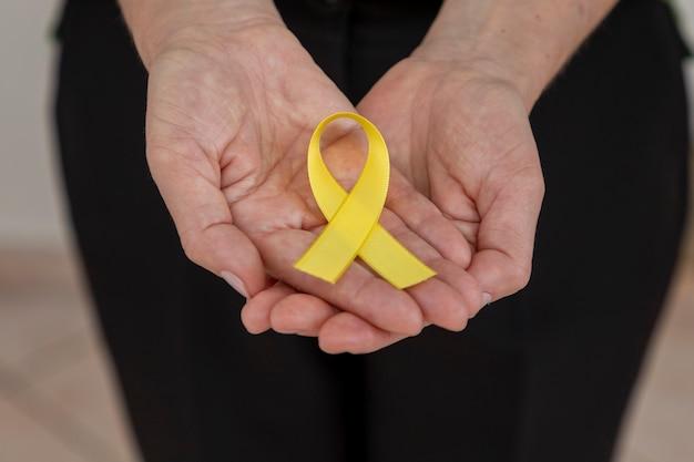 黄色いリボンを持っている手。黄色の9月、人生への愛。自殺予防キャンペーン