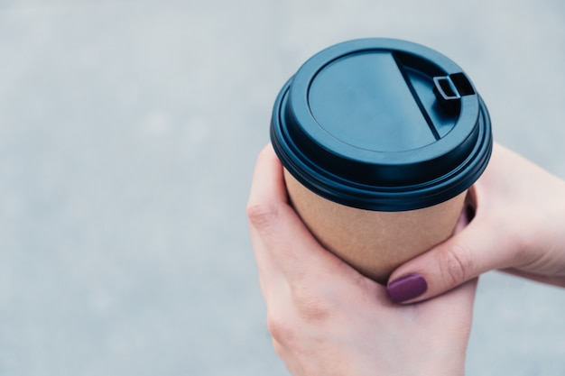 Hands holds coffee in brown cardboard cup with black cap