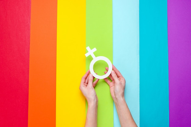 Hands holds female gender symbol on rainbow background