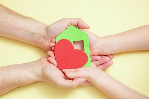 手は赤いハートの緑の紙の家を持っています。