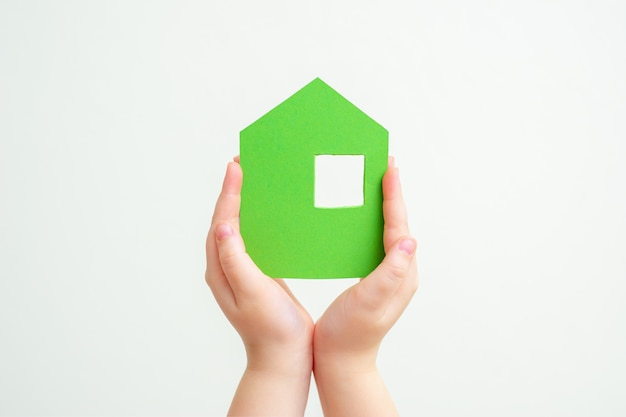 Hands holds green paper house