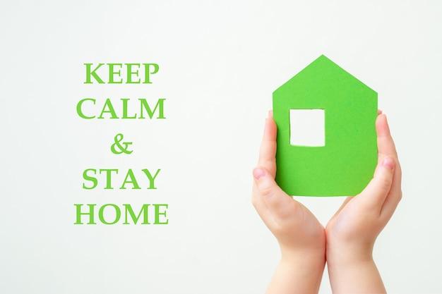 Руки держит зеленый бумажный дом.