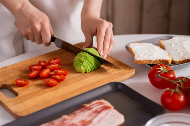 Hands of housewife with knife cutting fresh avocado and tomatoes on wooden board for sandwiches while cooking breakfast for herself