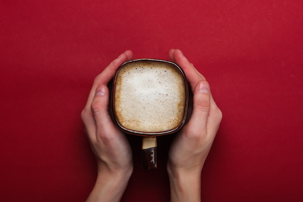 Руки обнимают чашку латте или капучино на красном фоне. кофе с молоком. вид сверху