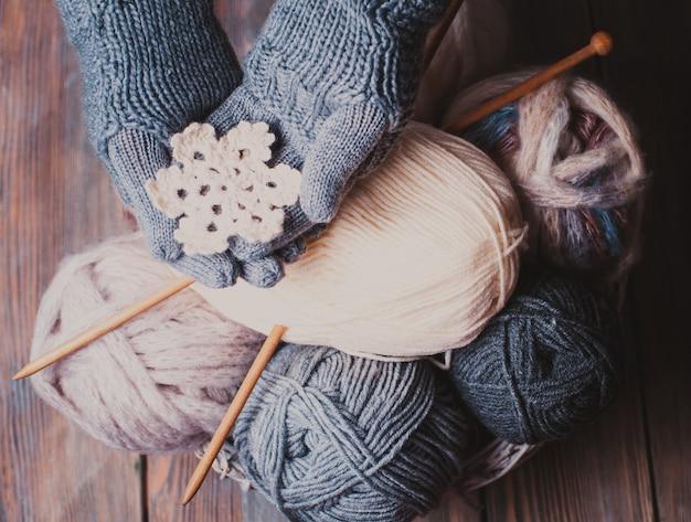 冬のシンボルとして白いニットスノーフレークを保持している灰色の手袋の手