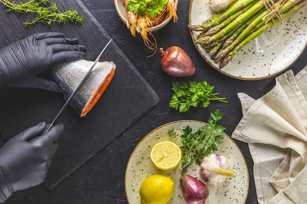 セラミックプレートでハーブ、タマネギ、ニンニク、アスパラガス、エビ、エビを囲まれた黒い石のまな板に黒い手袋の手がマス魚をカットしました。黒いコンクリートテーブルの表面。健康的なシーフードの背景