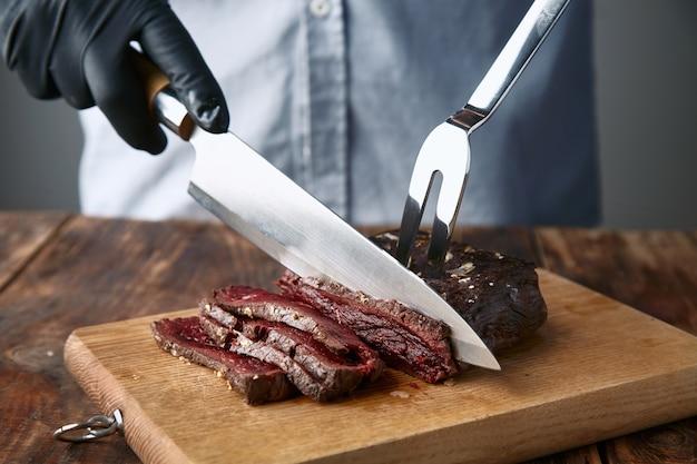 Руки в черных перчатках нарезают стейк из китового мяса средней прожарки ножом и вилкой