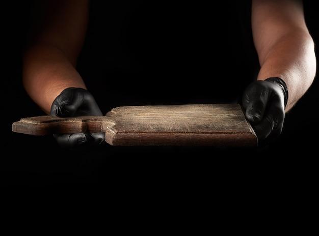 黒のラテックス手袋の手が空のヴィンテージの木製のまな板を保持