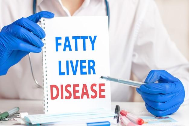 종이와 파란색 장갑에 손입니다. 테이블에 텍스트 지방 간 질환, 청진 기 및 의료 문서와 함께 종이 시트. 병원, 클리닉 및 의료 사업에 대한 개념 의료.