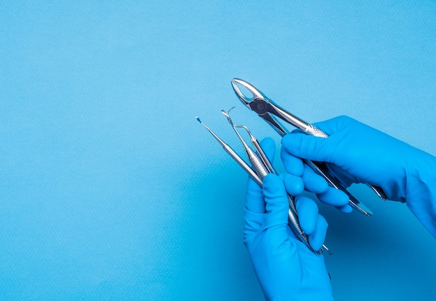 水色の背景に歯科用クランプと手術棒を保持している青い手袋の手