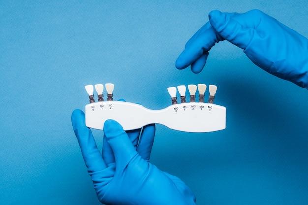 青い背景に歯科用カラーパレットを保持している青い手袋の手