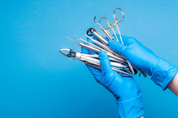 Руки в синих перчатках держат стоматологическое оборудование и металлические инструменты на синем фоне