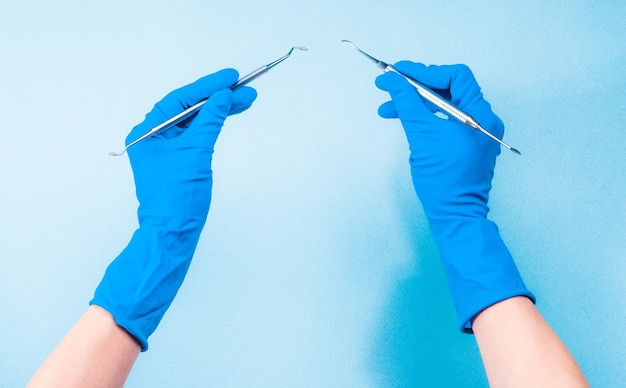 Руки в синих перчатках, держа стоматологические инструменты на голубом фоне