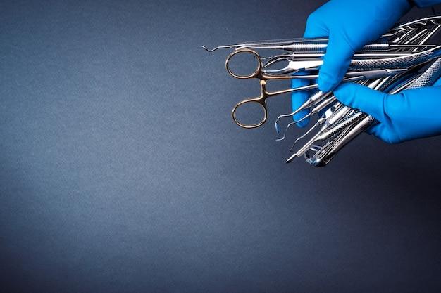 Руки в синих перчатках держат металлическое стоматологическое оборудование на сером фоне с копией пространства