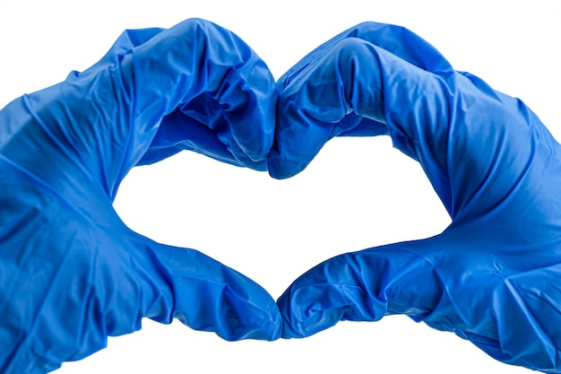 Руки в синих перчатках, показаны сердце на белом.