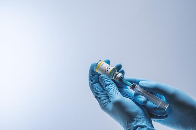 青いラテックス手袋をはめた手が注射器にガラスバイアルからのワクチンを充填します