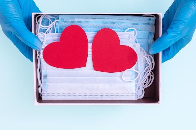 Руки в синих медицинских перчатках держат открытую подарочную коробку с защитными медицинскими масками