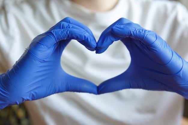 Руки в синих медицинских перчатках держат пальцы в форме сердца. жест рукой.