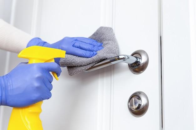 ぼろとスプレー洗剤でドア ハンドルを消毒する手袋をはめた手
