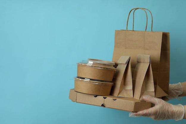 手袋をはめた手は、青のテイクアウト食品の配達容器を保持します