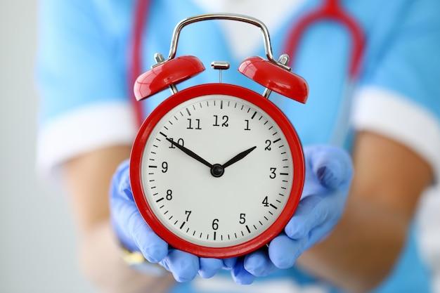 赤い目覚まし時計を保持している手袋の手