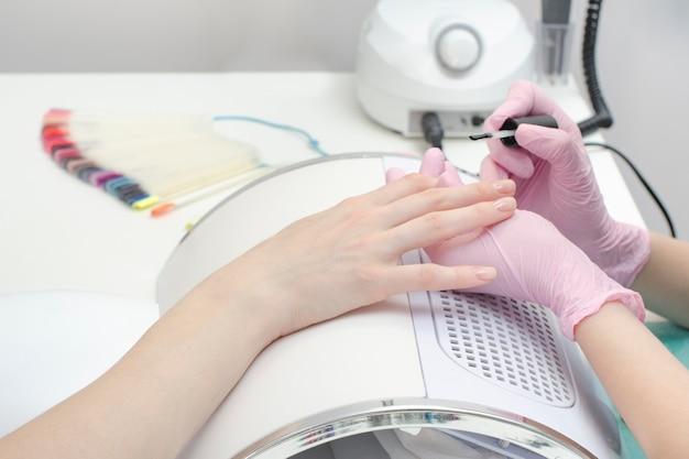 手袋をはめた手がマニキュアのサロンで爪を塗ります。閉じる