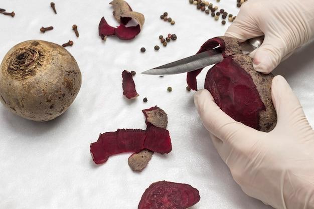 장갑을 든 손은 사탕무 껍질을 벗 깁니다. 건강한 겨울 음식. 흰색 표면. 평면도