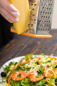 장갑을 낀 손은 강판에 치즈를 문지릅니다.