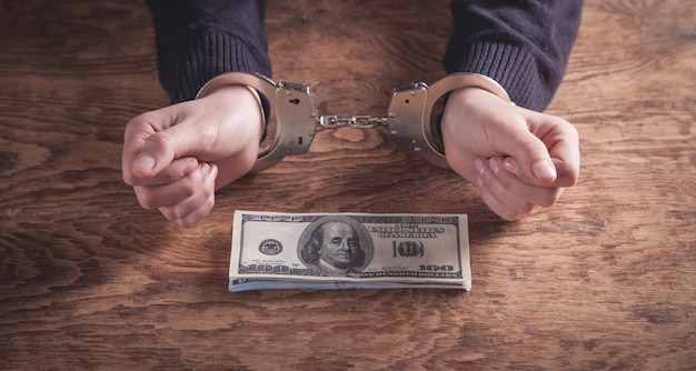 ドル紙幣を持っている手錠の手。腐敗