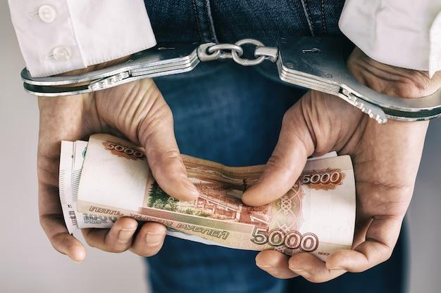 賄賂の逮捕に関するルーブルの概念を持つ手錠の手