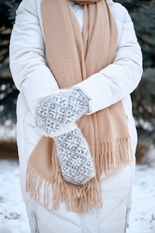 ニットミトンの手。冬のライフスタイル。スタイリッシュな暖かい服を着ています。暖かい服を着た女性