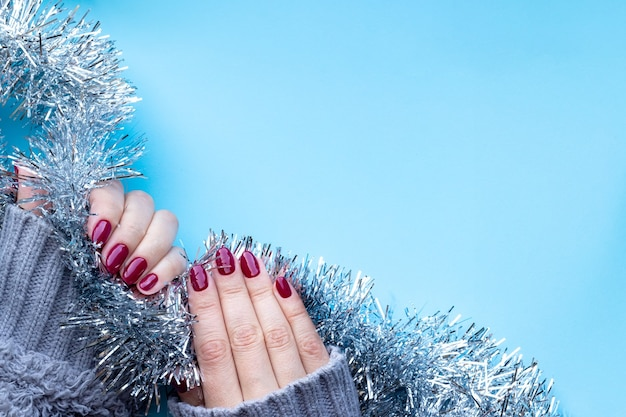 光沢のあるバーガンディの爪が付いたニットセーターの手