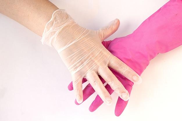 Руки в латексных и резиновых перчатках на белом