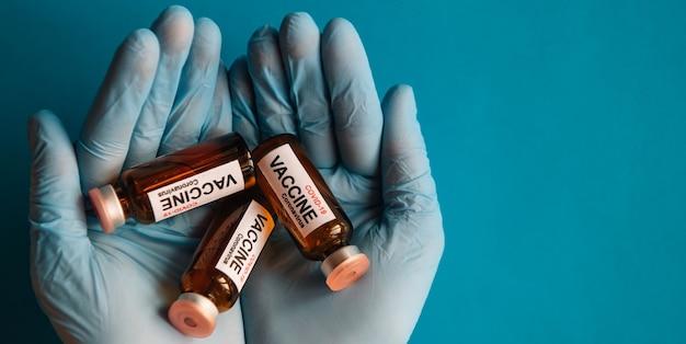 새로운 코로나바이러스 백신 바이알을 들고 있는 라텍스 장갑에 손을 얹고 파란색 배경에 닫습니다. covid-19 전염병에 맞서는 의료진과 과학자. 자원 봉사자에 대한 테스트 준비가 된 약. 공간을 복사합니다.