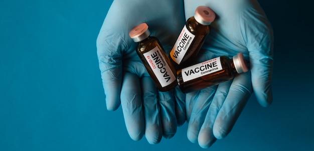 Руки в латексных перчатках держат флаконы с новой вакциной против коронавируса, крупным планом на синем фоне. медики и ученые против пандемии covid-19. лекарство готово к испытанию на добровольцах. скопируйте пространство.