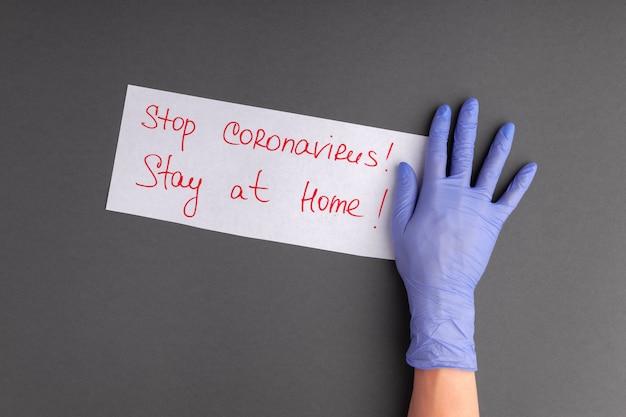 Руки в медицинских перчатках держит лист бумаги с красной надписью стоп коронавирус, оставайся дома