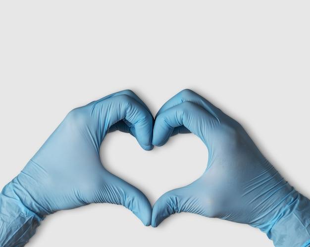 コピースペースと白い背景の上のハートの形の医療用手袋の手。
